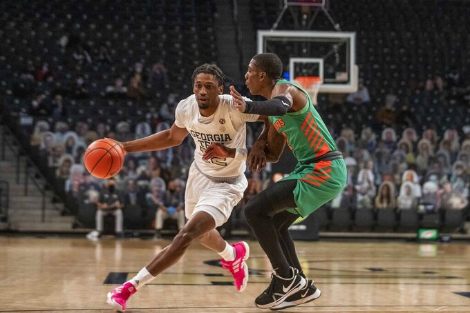 Georgia Tech forward Khalid Moore (12) dribbles past Florida A&M guard Kamron Reaves (2) during the first half of an NCAA college basketball game in Atlanta, Friday, Dec. 18, 2020. (Alyssa Pointer/Atlanta Journal-Constitution via AP)
