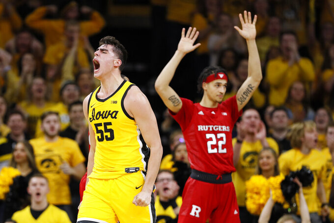 Iowa center Luka Garza celebrates in front of Rutgers guard Caleb McConnell (22) after making a basket during the first half of an NCAA college basketball game, Wednesday, Jan. 22, 2020, in Iowa City, Iowa. (AP Photo/Charlie Neibergall)