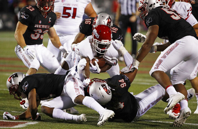 Fresno State Bulldogs running back Dejonte O'Neal, center, is tackled by UNLV Rebels defensive lineman Kolo Uasike (94) after a gain during the first half of an NCAA college football game Saturday, Nov. 3, 2018, in Las Vegas. (AP Photo/John Locher)