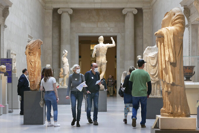 Two visitors wear masks as they walk through the Metropolitan Museum of Art in New York, Tuesday, March 10, 2020.  New York continued grappling  with the new coronavirus, as case numbers, school closings and other consequences grew.  (AP Photo/Seth Wenig)