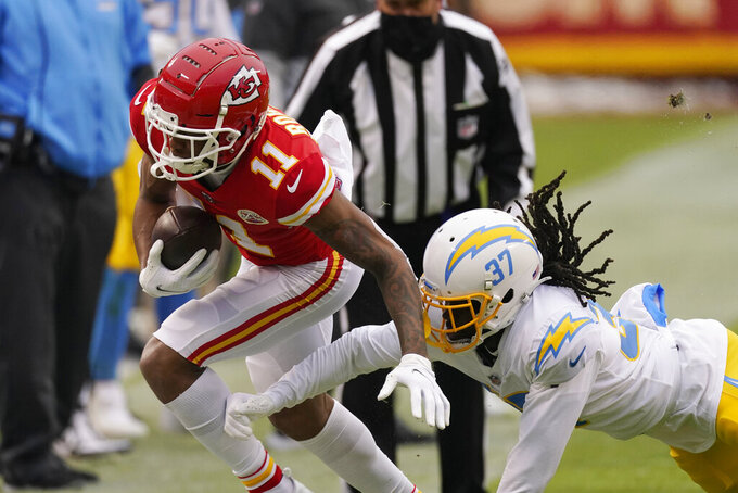 Kansas City Chiefs wide receiver Demarcus Robinson (11) runs from Los Angeles Chargers cornerback Tevaughn Campbell, right, after catching a pass during the first half of an NFL football game, Sunday, Jan. 3, 2021, in Kansas City. (AP Photo/Charlie Riedel)