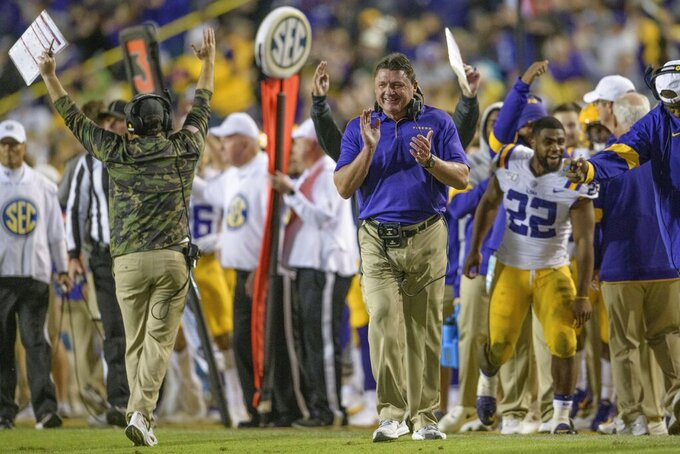 LSU coach Ed Orgeron celebrates as LSU running back John Emery Jr. runs for a touchdown against Arkansas during the second half of an NCAA college football game in Baton Rouge, La., Saturday, Nov. 23, 2019. (AP Photo/Matthew Hinton)