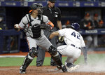 Baltimore Orioles catcher Jesus Sucre, left, looks to throw after Tampa Bay Rays' Tommy Pham scored on a sacrifice fly by Yandy Diaz during the fourth inning of a baseball game Tuesday, April 16, 2019, in St. Petersburg, Fla. (AP Photo/Chris O'Meara)