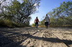 Pamela Rivas, left, with her son Michael Maldonado, right, walks on her property that runs along the Rio Grande in Los Ebanos, Texas, Friday, Nov. 20, 2020. The U.S. government has been trying to take Pamela Rivas' land for a border wall since before Joe Biden was vice president. (AP Photo/Eric Gay)