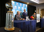The Holiday Bowl trophy towers in the foreground as USC head football coach Clay Helton and Iowa head football coach Kirk Ferentz speak to members of the media about the 2019 Holiday Bowl during a press conference on Thursday, Dec. 26, 2019, in San Diego, Calif. (Bryon Houlgrave/The Des Moines Register via AP)
