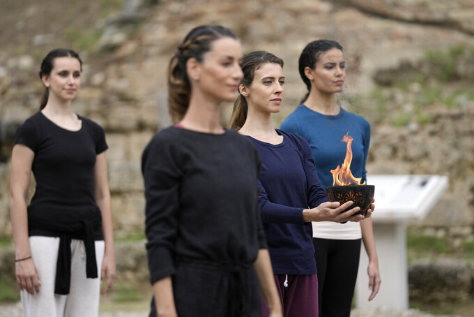 Actresses perform during the final rehearsal for the lighting of the Olympic flame at Ancient Olympia site, birthplace of the ancient Olympics in southwestern Greece, Sunday, Oct. 17, 2021. The flame will be transported by torch relay to Beijing, China, which will host the Feb. 4-20, 2022 Winter Olympics. (AP Photo/Petros Giannakouris)