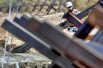 A government contractor, surrounded by existing Normandy barriers that separate Mexico and the United States, pours a concrete footer in preparation for a section of Pentagon-funded border wall along the Colorado River, Tuesday, Sept. 10, 2019 in Yuma, Ariz. A 30-foot high wall will replace the current five-mile section of border comprised of Normandy barriers and post-n-beam fencing. Construction began as federal officials revealed a list of Defense Department projects to be cut to pay for President Donald Trump's wall. (AP Photo/Matt York)