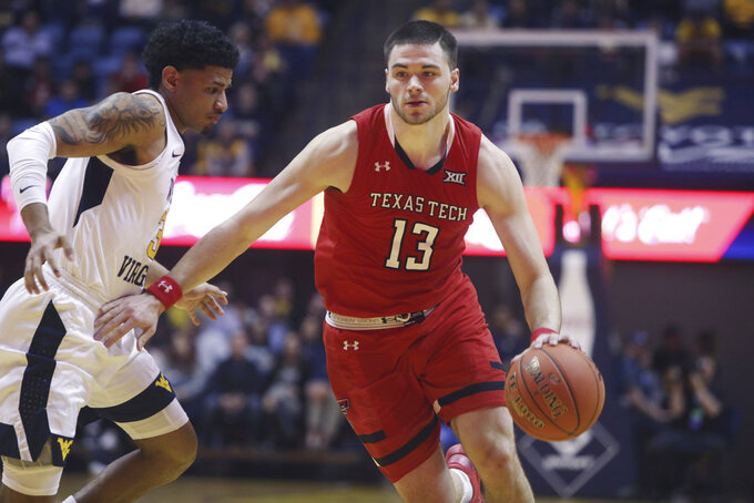 Texas Tech guard Matt Mooney (13) drives up court while defended by West Virginia guard James Bolden (3) during the first half of an NCAA college basketball game Wednesday, Jan. 2, 2019, in Morgantown, W.Va. (AP Photo/Raymond Thompson)