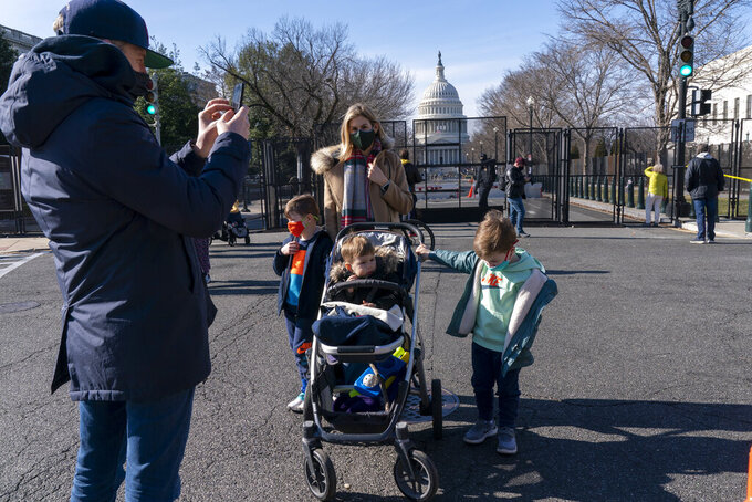 Gavin Coleman, owner of The Dubliner Restaurant, takes a photograph of his wife, Alexandra Coleman, and their sons, Henry, 6, Taylor, 4, and Peter, 2, by the anti-scaling fence protecting the U.S. Capitol compound, Saturday, Jan. 16, 2021, in Washington, as security is increased ahead of the inauguration of President-elect Joe Biden and Vice President-elect Kamala Harris. The Colemans live in the Capitol Hill neighborhood around the corner from the Capitol and are re-opening their restaurant to accommodate diners staying in the hotel above their restaurant for inauguration. (AP Photo/Jacquelyn Martin)