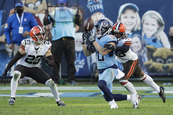 Tennessee Titans wide receiver Adam Humphries (10) loses control of the ball as he is hit by Cleveland Browns cornerback Terrance Mitchell (39) in the second half of an NFL football game Sunday, Dec. 6, 2020, in Nashville, Tenn. The Browns intercepted the ball on the play. (AP Photo/Ben Margot)