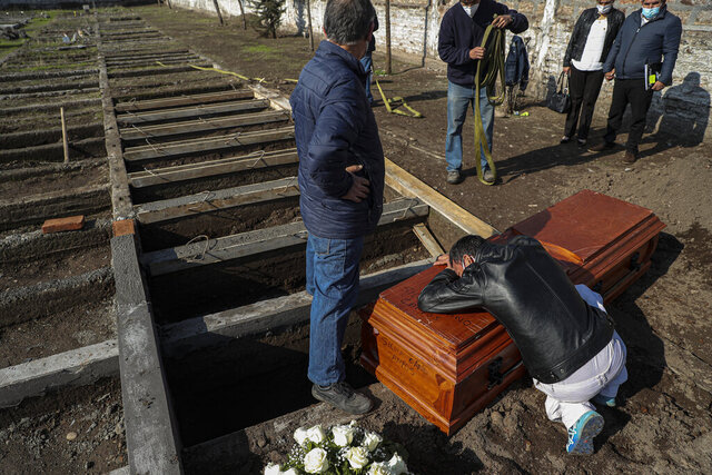 Peruvian migrant Jose Collantes grieves as he cries on the coffin that contains the remains of his wife Silvia Cano, who died due to COVID-19 complications, according to Collantes, at a Catholic cemetery in Santiago, Chile, Friday, July 3, 2020. (AP Photo/Esteban Felix)