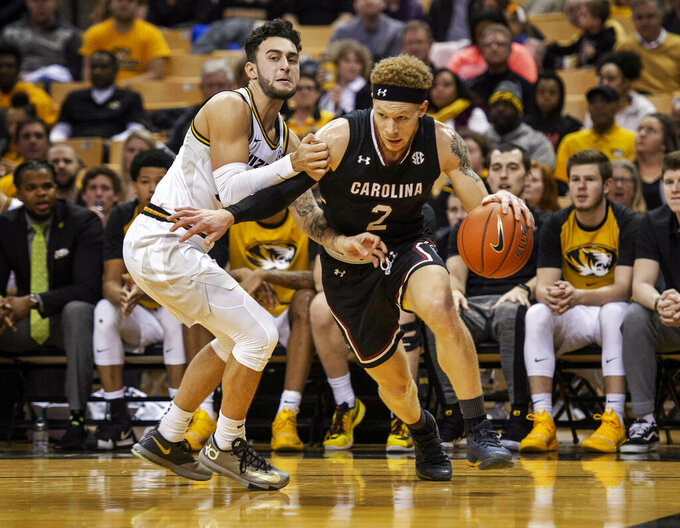 South Carolina's Hassani Gravett, right, dribbles past Missouri's Jordan Geist, left, during the first half of an NCAA college basketball game Saturday, March 2, 2019, in Columbia, Mo. (AP Photo/L.G. Patterson)