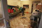 Keith Bainbridge, a volunteer for North West Ambulance Service, cleans up the Appleby and District Community First Responder Group premises in the aftermath of Storm Ciara, in Appleby-in-Westmorland, Cumbria, England, Monday, Feb. 10, 2020. Storm Ciara battered the U.K. and northern Europe with hurricane-force winds and heavy rains Sunday, halting flights and trains and producing heaving seas that closed down ports. Soccer games, farmers' markets and cultural events were canceled as authorities urged millions of people to stay indoors, away from falling tree branches. (Owen Humphreys/PA via AP)