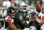 FILE - In this Nov. 2, 2008, file photo, Oakland Raiders quarterback JaMarcus Russell (2) fumbles the ball in front of Atlanta Falcons defensive end John Abraham (55) during the second quarter of their NFL football game in Oakland, Calif., Sunday, Nov. 2, 2008. The Raiders recovered the fumble. Russell got paid more than $39 million before being cut after three seasons in Oakland. (AP Photo/Paul Sakuma, File)