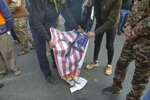Mourners burn a U.S. flag during the funeral of Iran's top general Qassem Soleimani and Abu Mahdi al-Muhandis, deputy commander of Iran-backed militias in Iraq known as the Popular Mobilization Forces, in Baghdad, Iraq, Saturday, Jan. 4, 2020. Thousands of mourners chanting