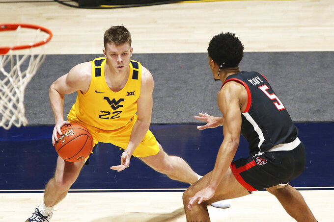 West Virginia guard Sean McNeil (22) is defend by Texas Tech guard Micah Peavy (5) during the first half of an NCAA college basketball game Monday, Jan. 25, 2021, in Morgantown, W.Va. (AP Photo/Kathleen Batten)