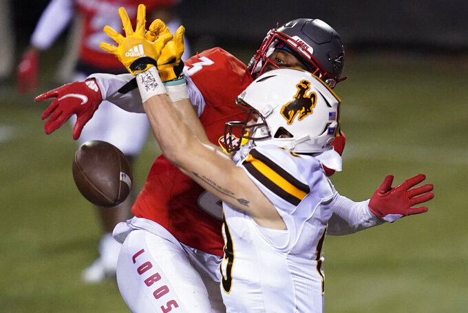 Wyoming wide receiver Ayden Eberhardt, right, misses a catch while covered by New Mexico safety Patrick Peek (3) during the second half of an NCAA college football game Saturday, Dec. 5, 2020, in Las Vegas. (AP Photo/John Locher)