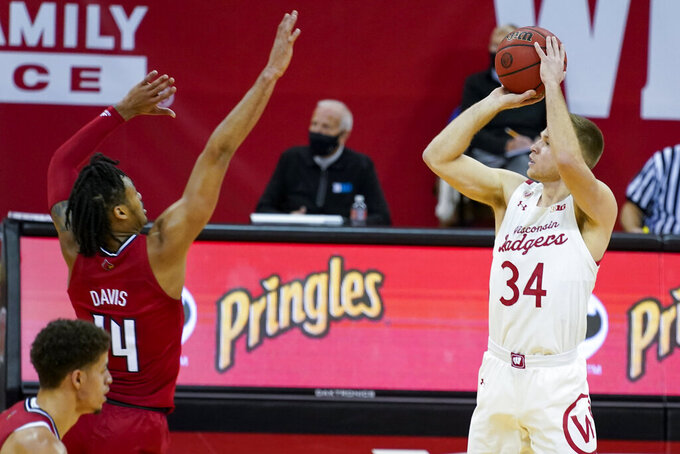 Wisconsin's Brad Davison (34) shoots a 3-point basket against Louisville's Dre Davis (14) during the first half of an NCAA college basketball game Saturday, Dec. 19, 2020, in Madison, Wis. (AP Photo/Andy Manis)