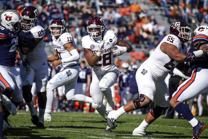 Texas A&M running back Isaiah Spiller (28) carries the ball during the first half of an NCAA college football game against Auburn on Saturday, Dec. 5, 2020, in Auburn, Ala. (AP Photo/Butch Dill)
