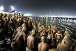In this Jan. 27, 2019, photo, Hindu men take dip for becoming Naga Sadhus or naked holy men at Sangam, the confluence of three holy rivers during the Kumbh Mela or pitcher festival in Prayagraj Uttar Pradesh state, India. At every Kumbh, including this year's, thousands of devotees were initiated into the reclusive sect of the Naga Sadhus, naked, ash-smeared cannabis-smoking Hindu warriors and onetime-armed defenders of the faith who for centuries have lived as ascetics in jungles and caves. (AP Photo/ Rajesh Kumar Singh)