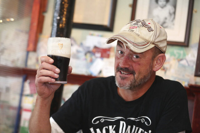 Customer Angus Fleming poses with a pint of Guinness in Mary Mac's pub, Dublin, Ireland, as Ireland further eases restrictions with pubs that serve food, restaurants, cafes, hairdressers and barbers among those allowed to reopen following the coronavirus lockdown, Monday June 29, 2020.  Life became ever so slightly more normal in Ireland on Monday as some restrictions are eased, with pints being pulled in pubs, locked-down hair having locks trimmed and churches admitted congregants, all for the first time since March. (Niall Carson/PA via AP)