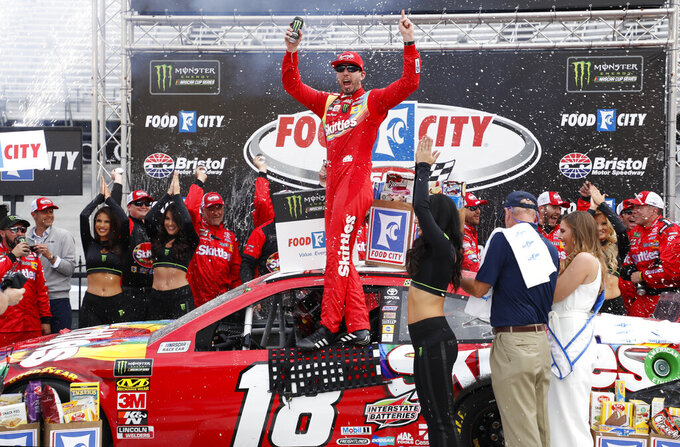 Driver Kyle Busch (18) celebrates after winning a NASCAR Cup Series auto race, Sunday, April 7, 2019, in Bristol, Tenn. (AP Photo/Wade Payne)