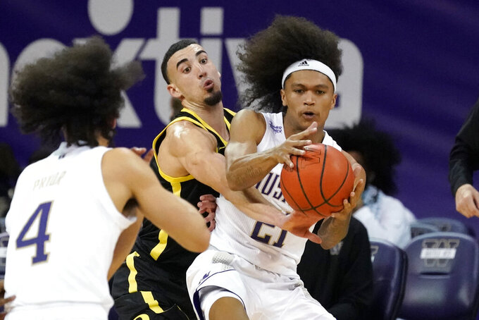 Washington's RaeQuan Battle (21) reaches for a pass from Nate Pryor (4) as Oregon's Chris Duarte defends during the second half of an NCAA college basketball game Saturday, Dec. 12, 2020, in Seattle. (AP Photo/Elaine Thompson)