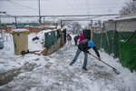 Residents clear the snow at the entrance of a house at the Canada Real shanty town, outside Madrid, Spain, Friday, Jan. 8, 2021. An illegal informal settlement that has spread over several decades as poor Spaniards, Roma people and Moroccan migrants sought a place to live, La Cañada's poor housing and make-shift shacks stretches some 14 kilometers (9 miles) along what was once a drover's pathway on the Spanish capital's southeastern industrial outskirts. Nowadays, it's home to some 7,500 people of low or no income. (AP Photo/Manu Fernandez)