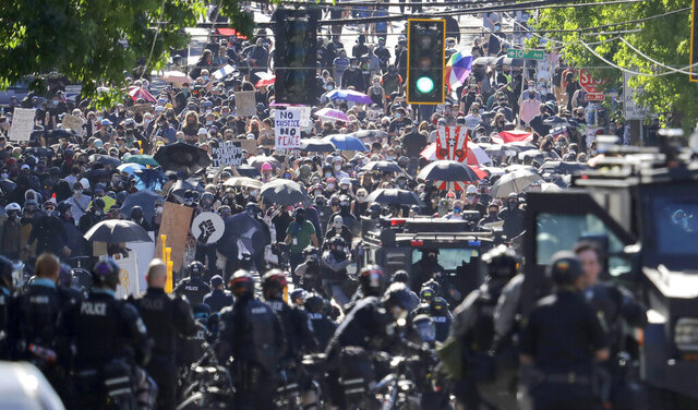 FILE - In this July 25, 2020, file photo, police clash with protesters during a Black Lives Matter protest near the Seattle Police East Precinct headquarters in Seattle. New York, Seattle and Portland, three cities recently labeled