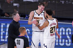 Denver Nuggets head coach Michael Malone, left, celebrates the team's win over the Los Angeles Clippers with center Nikola Jokic (15) and guard Jamal Murray (27) in an NBA conference semifinal playoff basketball game Tuesday, Sept. 15, 2020, in Lake Buena Vista, Fla. (AP Photo/Mark J. Terrill)