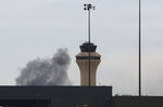 Smoke rises behind an air traffic control tower on west side of Dallas/Fort Worth International Airport in Grapevine, Dallas, Wednesday, Feb. 13, 2019. Flights at Dallas' two major airports were temporarily halted after air traffic controllers were forced to evacuate a building because of smoke, and the resulting flight delays are expected to continue for hours. (AP Photo/LM Otero)