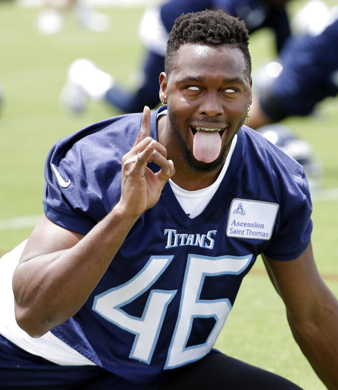 Tennessee Titans defensive back Joshua Kalu makes a face for the cameras as he stretches during an organized team activity at the Titans' NFL football training facility Tuesday, June 11, 2019, in Nashville, Tenn. (AP Photo/Mark Humphrey)