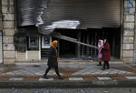People walk past a bank that was burned during recent protests, in Shahriar, Iran, some 40 kilometers (25 miles) southwest of the capital, Tehran, Wednesday, Nov. 20, 2019. Protests over government-set gasoline prices rising struck at least 100 cities and towns, spiraling into violence that saw banks, stores and police stations attacked and burned. (AP Photo/Vahid Salemi)