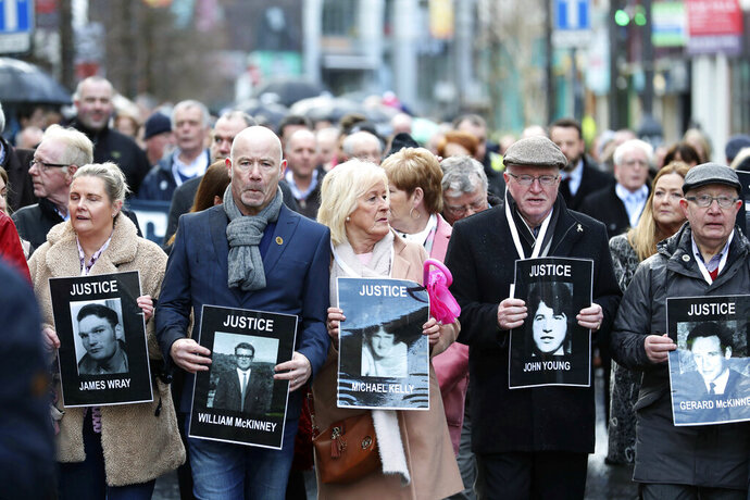 Families hold photographs of the victims of Bloody Sunday and march through the Bogside in Londonderry, Northern Ireland, Thursday March 14, 2019. A former British soldier is set to be prosecuted in connection with the deaths of two civil rights protesters in Northern Ireland more than 40 years ago, part of an event known as Bloody Sunday. (Liam McBurney/PA via AP)
