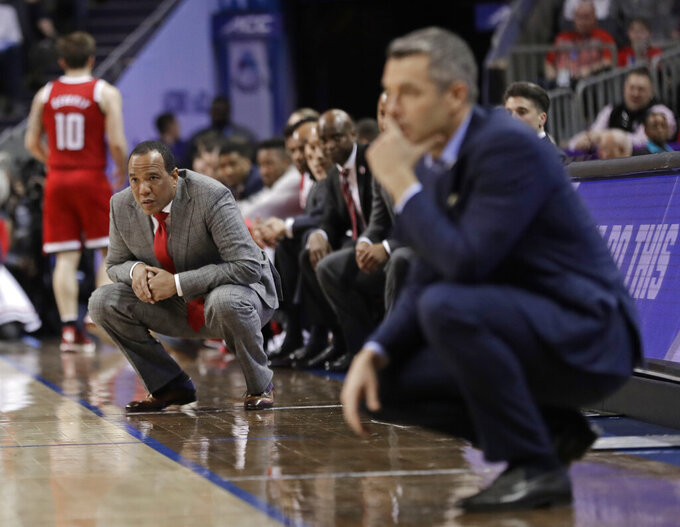 North Carolina State head coach Kevin Keatts, left, and Virginia head coach Tony Bennett, right, watch their teams play during the first half of an NCAA college basketball game in the Atlantic Coast Conference tournament in Charlotte, N.C., Thursday, March 14, 2019. (AP Photo/Nell Redmond)