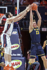 Michigan forward Ignas Brazdeikis (13) steals a pass in tended for Illinois forward Giorgi Bezhanishvili (15) during the second half of an NCAA college basketball game in Champaign, Ill., Thursday, Jan. 10, 2019. (AP Photo/Rick Danzl)
