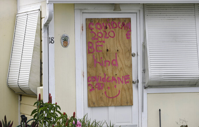 A boarded up home is shown, Saturday, Aug. 1, 2020, in Briny Breezes, Fla. Hurricane Isaias has snapped trees and knocked out power while blowing through the Bahamas on Saturday. It's headed toward the Florida coast, where officials have closed beaches, parks and coronavirus testing sites. (AP Photo/Wilfredo Lee)