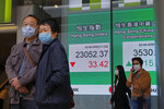People walk past an electronic board showing Hong Kong share index outside a local bank in Hong Kong, Thursday, April 2, 2020. Asian stocks were meandering Thursday after a White House warning that as many as 240,000 Americans might die of the coronavirus sent Wall Street tumbling and signs of the outbreak's global economic cost increased.(AP Photo/Kin Cheung)