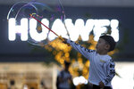 In this photo taken Monday, May 20, 2019, a child plays with bubbles near the logo for tech giant Huawei in Beijing. The Trump administration's sanctions against Huawei have begun to bite even though their dimensions remain unclear. U.S. companies that supply the Chinese tech powerhouse with computer chips saw their stock prices slump Monday, and Huawei faces decimated smartphone sales with the anticipated loss of Google's popular software and services. (AP Photo/Ng Han Guan)