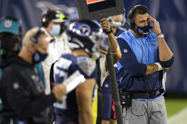 """FILE- In this Oct. 13, 2020, file photo, Tennessee Titans head coach Mike Vrabel, right, reacts during the second quarter of an NFL football game against the Buffalo Bills, in Nashville, Tenn. The NFL and the NFL Players Association found instances when the Titans failed to wear masks at all times and were """"insufficiently clear"""" to players about not meeting or working out once the facility closed in a review given to the team Monday, Oct. 19, 2020, a person familiar with the investigation told The Associated Press.But the person familiar with the review says there was no discussion of any discipline for an individual including general manager Jon Robinson, coach Mike Vrabel or any players, and there was no discussion of punishment, including forfeitures or draft picks.(AP Photo/Brett Carlsen, File)"""