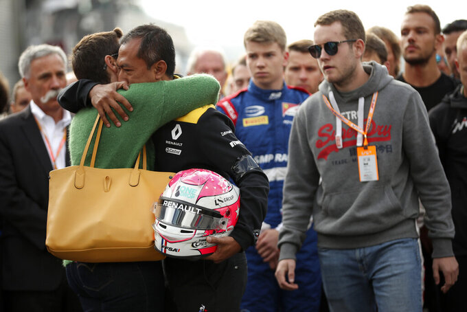 The mother, left, and brother, second right, of Anthoine Hubert during a moment of silence for Formula 2 driver Anthoine Hubert at the Belgian Formula One Grand Prix circuit in Spa-Francorchamps, Belgium, Sunday, Sept. 1, 2019. The 22-year-old Hubert died following an estimated 160 mph (257 kph) collision on Lap 2 at the high-speed Spa-Francorchamps track, which earlier Saturday saw qualifying for Sunday's Formula One race. (AP Photo/Francisco Seco)