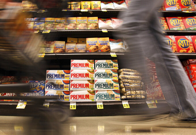 FILE - In this Feb. 9, 2011, file photo, a shopper passes a shelf of Nabisco products, a Mondelez International brand: Premium saltines, Triscuits, Ritz crackers and Wheat Thins, at a Ralphs Fresh Fare supermarket in Los Angeles. A tentative contract agreement reached between snack company Mondelez and striking union workers could end a walkout that began last month. The Bakery, Confectionery, Tobacco Workers and Grain Millers International Union and Mondelez issued separate statements Wednesday, Sept. 15, 2021, announcing a tentative deal, but neither would discuss the terms, The Richmond Times-Dispatch reported. (AP Photo/Reed Saxon, File)