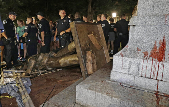 FILE - In this Aug. 20, 2018 file photo, police stand guard after the confederate statue known as Silent Sam was toppled by protesters on campus at the University of North Carolina in Chapel Hill, N.C.   Judge Allen Baddour ruled Wednesday, Feb. 12, 2020 that the Sons of Confederate Veterans didn't have standing to bring the lawsuit that led to the hastily arranged deal that gave them possession of the statue known as Silent Sam, along with $2.5 million to maintain it. He  vacated the deal and also dismissed the underlying lawsuit brought by the SCV.  Critics had questioned how the deal was quietly struck with the UNC Board of Governors and approved just before Thanksgiving.     (AP Photo/Gerry Broome, File)