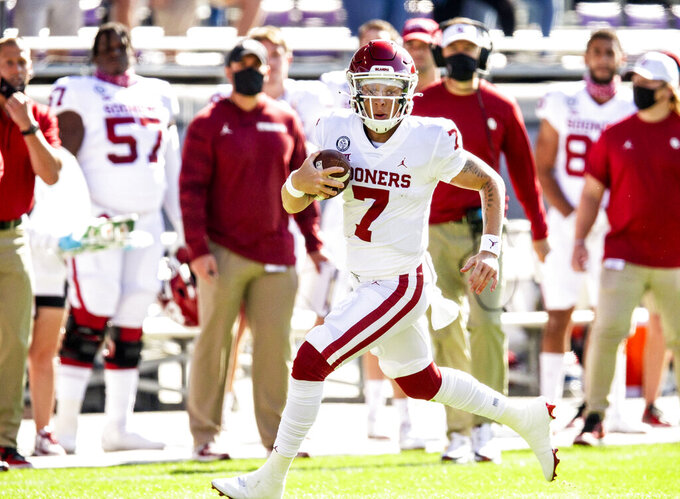 Oklahoma quarterback Spencer Rattler (7) carries the ball during the first half of an NCAA college football game against TCU, Saturday, Oct. 24, 2020, in Fort Worth, Texas. (AP Photo/Brandon Wade)