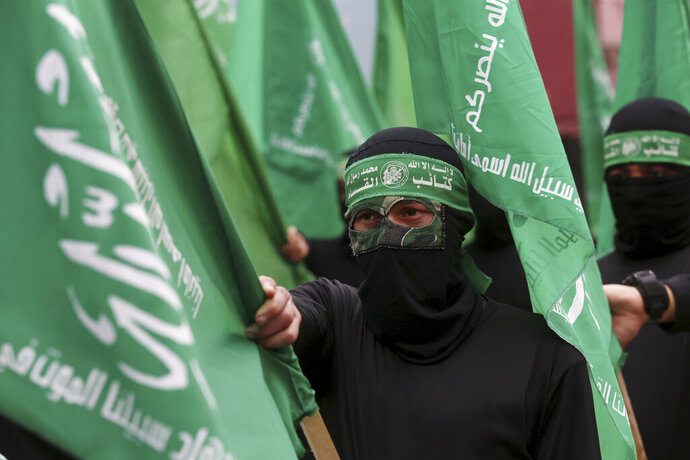 Masked Hamas militants wave their green flags during a protest against the Mideast plan announced by U.S. President Donald Trump, after the Friday prayer at the main road in Gaza City, Friday, Feb. 14, 2020. Arabic on the headband reads