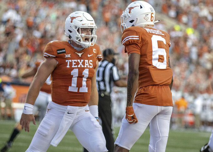 Texas quarterback Sam Ehlinger (11) celebrates with Joshua Moore (6) after a Texas touchdown against UTEP during the first quarter of an NCAA college football game Austin, Texas, Saturday, Sept. 12, 2020. (Ricardo B. Brazziell/Austin American-Statesman via AP)