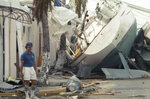 FILE- In this Sept. 20, 1989 file photo, Sid Kalmas stands guard over his damaged hotel in Christiansted, U.S. Virgin Island, after Hurricane Hugo slammed the island chain.  The storm destroyed 85% of the buildings in St. Croix and caused $1 billion in damage to Puerto Rico before making landfall in South Carolina. Hurricane Hugo might have been the first modern U.S. storm ushering in an era of live TV coverage and large scale coastal evacuations. (AP Photo/Steve Helber, File)