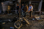 People check the aftermath of a car bomb blast in the city of Qamishli, northern Syria, Monday, Nov. 12, 2019. Three car bombs went off Monday in then city killing several and wounding tens of people. (AP Photo/Baderkhan Ahmad)