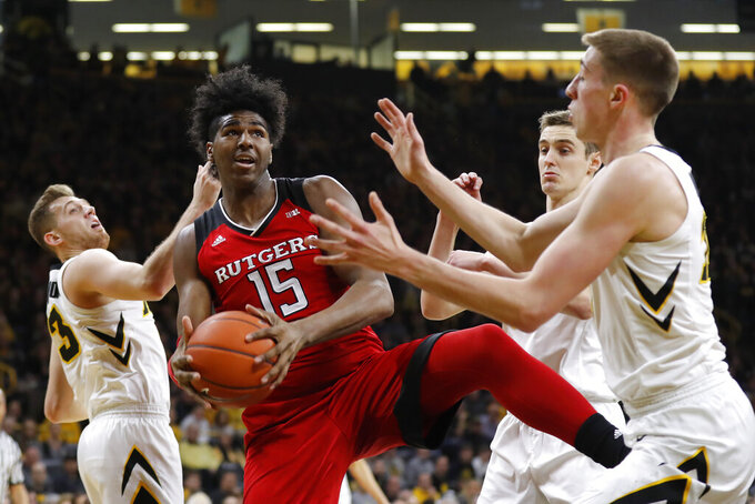 Rutgers center Myles Johnson (15) grabs a rebound between Iowa's Jordan Bohannon, left, Nicholas Baer and Joe Wieskamp, right, during the first half of an NCAA college basketball game, Saturday, March 2, 2019, in Iowa City, Iowa. (AP Photo/Charlie Neibergall)