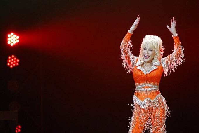 "FILE - Dolly Parton performs in concert on May 27, 2014, in Knoxville, Tenn. The Grammy-winning legend's 1980's hit ""9 to 5"" has been flipped by Squarespace, the company that helps users build and host their own websites, for a Super Bowl commercial debuting Tuesday, Feb. 2, 2021. Oscar winner Damien Chazelle of ""La La Land"" fame directed the spot. (Photo by Wade Payne/Invision/AP, File)"